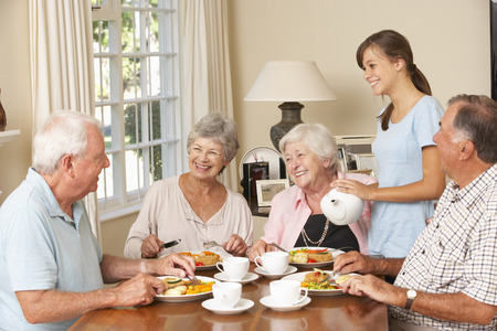 retirement community: Group Of Senior Couples Enjoying Meal Together In Care Home With Teenage Helper