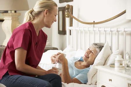 an elderly person: Health Visitor Talking To Senior Woman Patient In Bed At Home