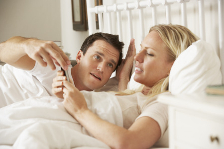 happy wife: Husband Complaing As Wife Uses Mobile Phone In Bed Stock Photo