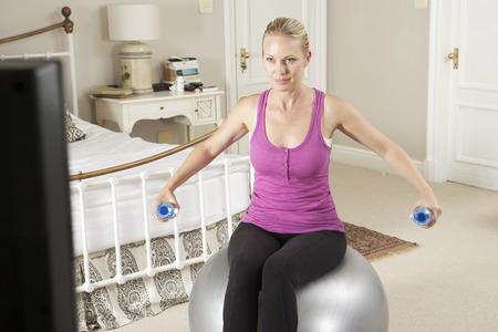 텔레비전에서 휘트니스 DVD를 보는 동안 운동을하는 여자