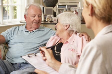 financial advisor: Retired Senior Couple Sitting On Sofa Talking To Financial Advisor
