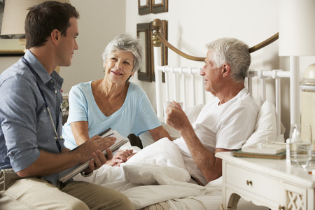 visit: Doctor On Home Visit Discussing Health Of Senior Male Patient With Wife