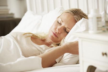 insomniac: Medication On Bedside Table Of Sleeping Woman Stock Photo