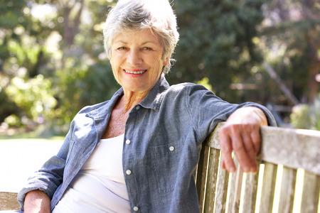 relaxando: Mulher sênior que relaxa no banco de parque