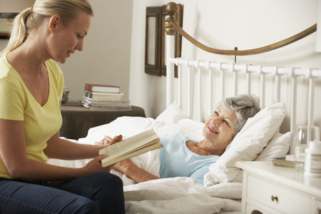 palliative: Adult Daughter Reading To Senior Female Parent In Bed At Home Stock Photo