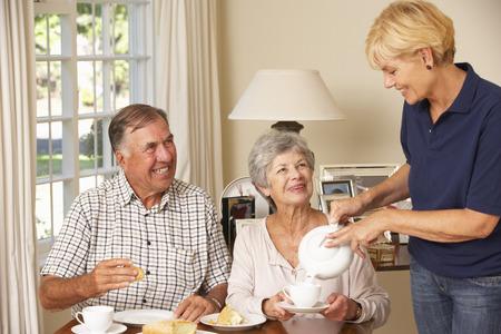 personas ayudando: Pares mayores que disfrutan del té de tarde juntos en casa con Inicio Ayuda