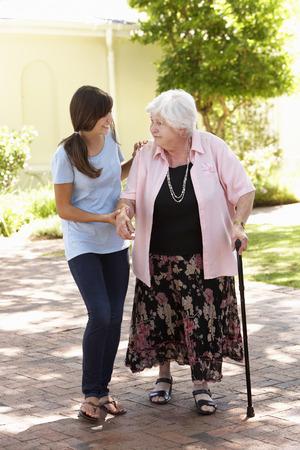 granddaughter: Teenage Granddaughter Helping Grandmother Out On Walk