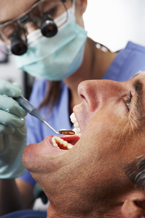 hygeine: Female Dentist Giving Male Patient Check Up Stock Photo