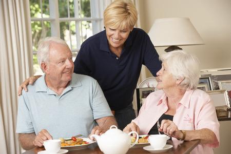 aide a domicile: Couple senior B�n�ficiant repas ensemble � la maison avec Home Help Banque d'images