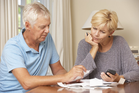 finance problems: Worried Mature Couple Checking Finances And Going Through Bills Together