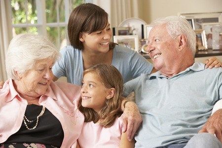 grandaughter: Grandparents Sitting On Sofa With Grandchildren Indoors