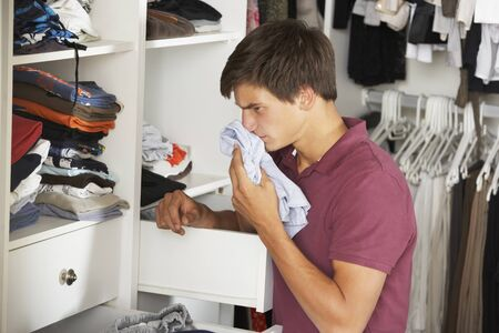 untidy: Teenage Boy Checking Freshness Of Clothes In Wardrobe