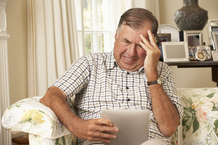 silver surfer: Frustrated Retired Senior Man Sitting On Sofa At Home Using Digital Tablet Stock Photo