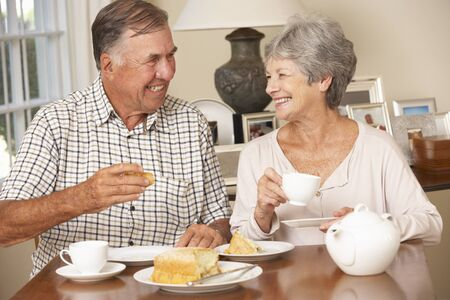 old people eating: Retired Senior Couple Enjoying Afternoon Tea Together At Home