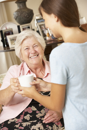 looking after: Teenage Granddaughter Making Grandmother Hot Drink At Home Stock Photo