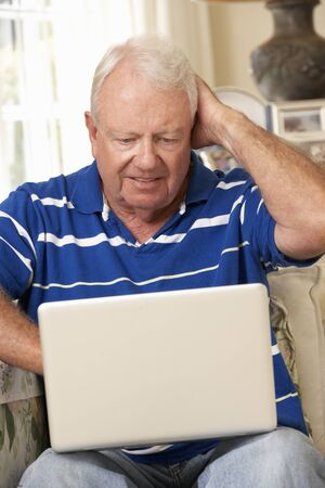 silver surfer: Frustrated Retired Senior Man Sitting On Sofa At Home Using Laptop Stock Photo