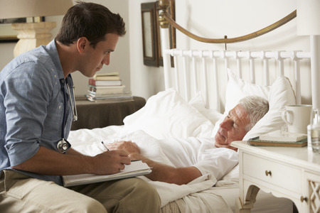 palliative: Doctor Talking With Senior Male Patient In Bed At Home Stock Photo