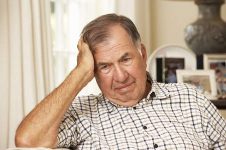 unhappy man: Unhappy Retired Senior Man Sitting On Sofa At Home