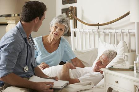 marido y mujer: Doctor Home Visit Discutiendo Salud De Paciente masculino mayor con la esposa Foto de archivo