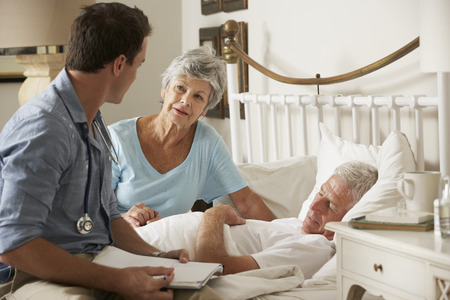home visit: Doctor On Home Visit Discussing Health Of Senior Male Patient With Wife