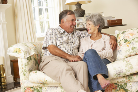 couple on couch: Retired Senior Couple Sitting On Sofa At Home Together Stock Photo