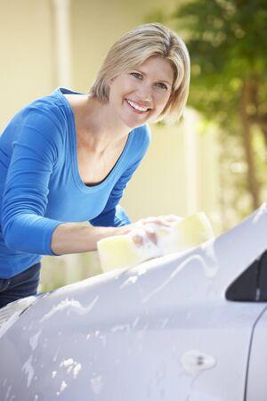 car clean: Woman Washing Car In Drive Stock Photo