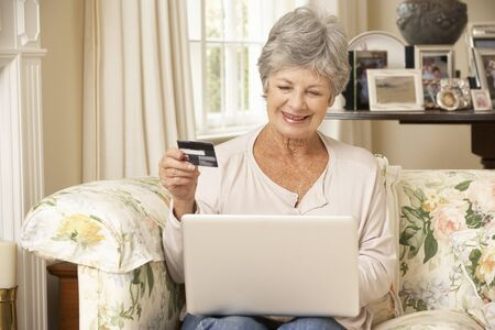 silver surfer: Retired Senior Woman Sitting On Sofa At Home Using Laptop To Make Online Purchase