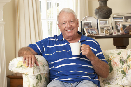 old man happy: Retired Senior Man Sitting On Sofa Drinking Tea At Home