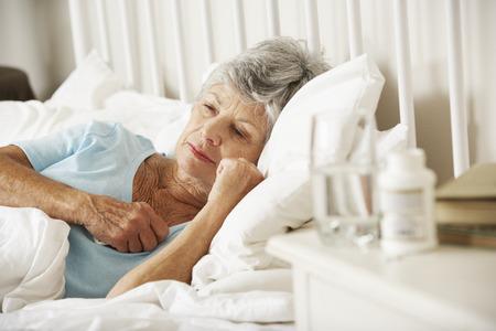 잠들지 않는 노인 여성의 머리맡 테이블에 약물