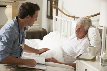 Doctor Talking With Senior Male Patient In Bed At Home Stock fotó