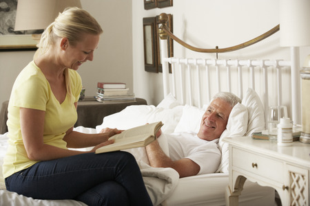 elderly care: Adult Daughter Reading To Senior Male Parent In Bed At Home