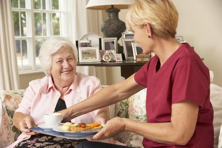 老人ホームで食事と年配の女性を提供するヘルパー