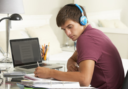 Teenage Boy Studying At Desk In Bedroom Wearing Headphones Stock Photo