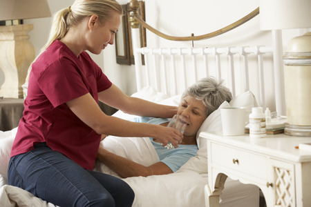 Health Visitor Giving Senior Woman Glass Of Water In Bed At Home Stock fotó