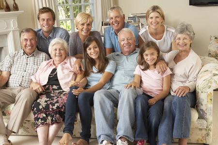 familie: Grote familie Op Bank Binnenshuis Stockfoto