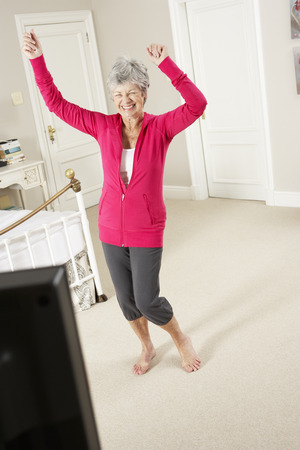 whilst: Senior Woman Exercising Whilst Watching Fitness DVD On Television
