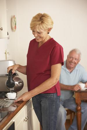 aide a domicile: Accueil Aide Partage tasse de th� avec Homme senior En cuisine Banque d'images
