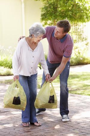 ayudando: Hombre ayudar a la mujer mayor con Compras
