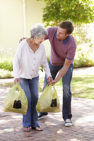 helping up: Man Helping Senior Woman With Shopping