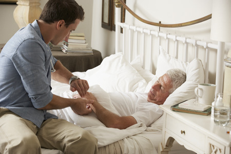 taking pulse: Doctor Taking Pulse Of Senior Male Patient In Bed At Home Stock Photo