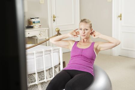 home keeping: Woman Exercising Whilst Watching Fitness DVD On Television