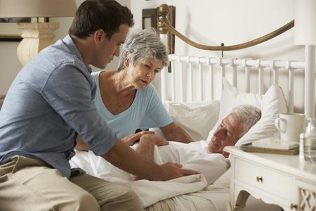 家庭訪問の妻とシニアの男性患者の健康を議論する医師