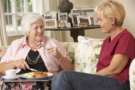 haushaltshilfe: Helper Serving Ältere Frau mit Mahlzeit im Heim Lizenzfreie Bilder