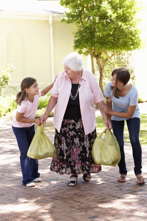 care in the community: Grandchildren Helping Grandmother To Carry Shopping