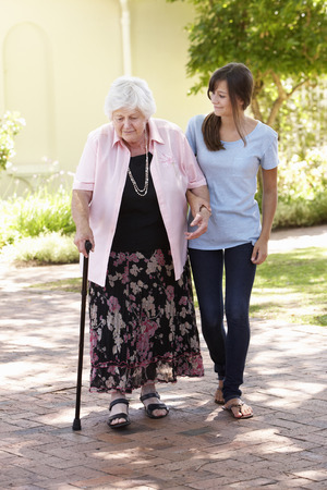 people walking: Teenage Granddaughter Helping Grandmother Out On Walk