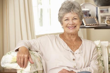 señora mayor: Jubilado mayor de la mujer que se sienta en el sofá en casa