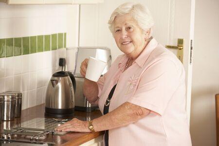 independencia: Retirado de la mujer mayor en la cocina haciendo Bebida caliente