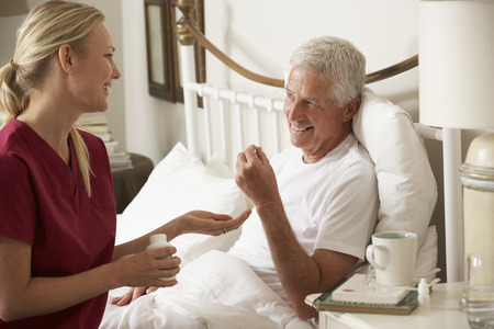 Health Visitor Giving Senior Male Medication In Bed At Home Stockfoto