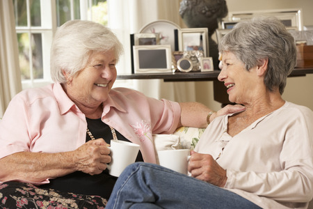 chatting: Two Retired Senior Female Friends Sitting On Sofa Drinking Tea At Home Stock Photo