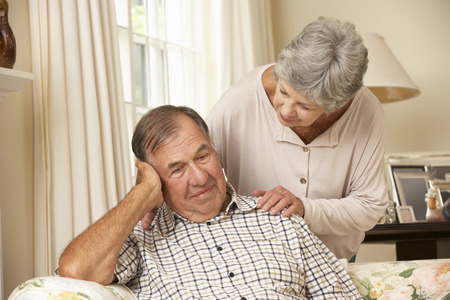 Senior Woman Comforting Unhappy Husband At Home
